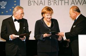 Момент вручения Ангеле Меркель сертификата с золотой медалью за создание благополучия еврейского народа и государства Израиль